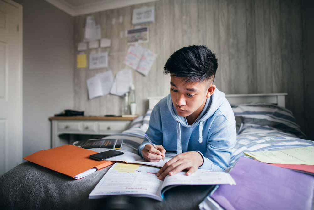 Student doing homework on bed