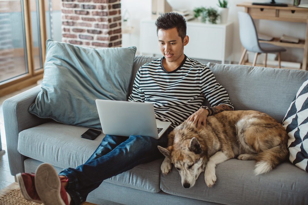 man sits on couch with dog while investing with laptop