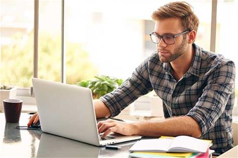 Man on home laptop reviews online investing