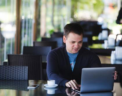 Man sitting down for coffee in quiet cafe opens laptop